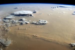 CAMELIA investiga el papel de los aerosoles minerales que se transportan en la atmósfera de la Tierra y Marte. (Arriba) Imagen de una tormenta de arena en la Tierra, sobre el desierto del Sahara en África, vista por el astronauta de la ESA Alexander Gerst desde la Estación Espacial Internacional. Crédito ESA. (Abajo) Imagen de una tormenta de polvo en Marte, visto por Mars Express, que capturó este frente ascendente de nubes de polvo, visible en la mitad derecha del cuadro, cerca del casquete polar norte de Marte (78 ° N / 106 ° E). Crédito: ESA/Mars Express.